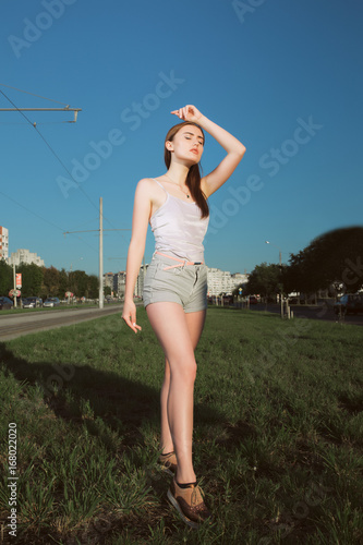 Poster Fashion portrait of brunette model posing on the avenue in sport clothes