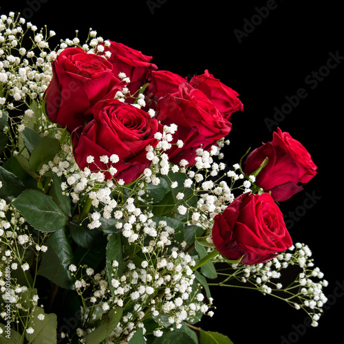 Bouquet of red roses and white wildflowers on a black background