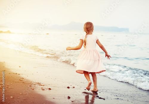 Summer vacation. Little child running barefoot on the sand on seacoast.
