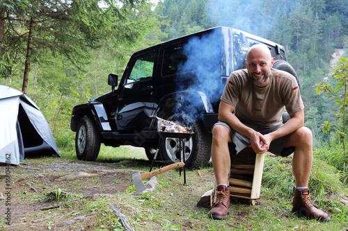 Mann grillt am Camping Platz vor SUV