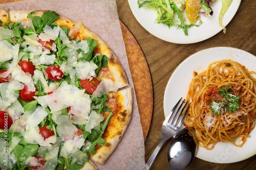 Italian Pizza, salad and Spaghetti on wooden table - 168066633