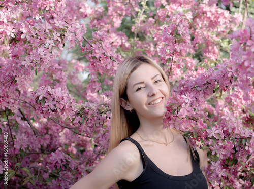 Beautiful smiling young woman near the blossoming spring tree. Portrait of pretty blond girl with long hair in pink flowers. Malus niedzwetzkyana blossoms. Lovely young woman looking happy.