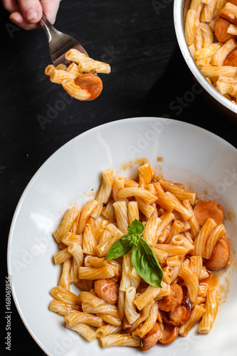 Pasta with sausages, tomato sauce and basil in a white plate on a tenor background - 168069856