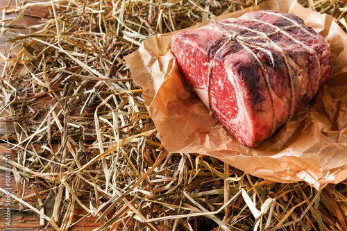 Sticker Raw aged prime black angus beef in craft papper on straw