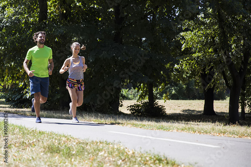 Sticker Young couple running in the park on a sunny day