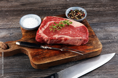 Raw fresh meat Ribeye Steak, seasoning and meat fork on dark background Poster