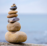 A stack of round stones standing on the shore of a sea - 168087811
