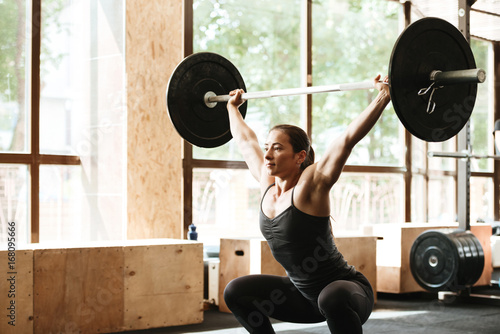 Sticker Sporty concentrated woman exercising with barbell