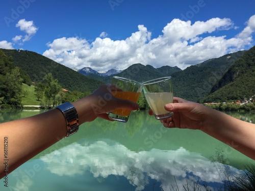 Zdjęcia na płótnie, fototapety, obrazy : Two hands holding juice glasses with Lake at Most na Soci, Slovenia, in background