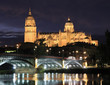 Salamanca skyline at night and Enrique Esteban Bridge over Tormes River in Spain