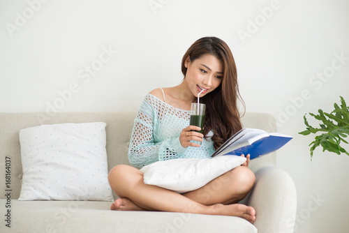 Sticker Woman relaxing on sofa in livingroom enjoying reading a book and drinking coffee.