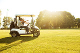 Two male golfers driving in a golf cart