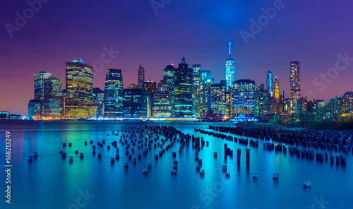 Tuinposter New York New York City at night. Manhattan skyline. Skyscrapers reflected in water. NY, USA