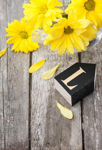 Fresh yellow daisy flowers, letter L