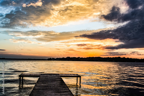 Sunset On Water / Aboat dock in alarge lake under orange and purple clouds at sunset.