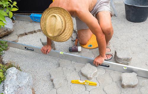 Mann bei der Pflasterreparatur in der Einfahrt, Ausrichten mit der Wasserwaage Poster
