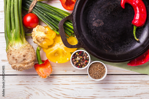 Various vegetables ingredients on wooden table around frying pan