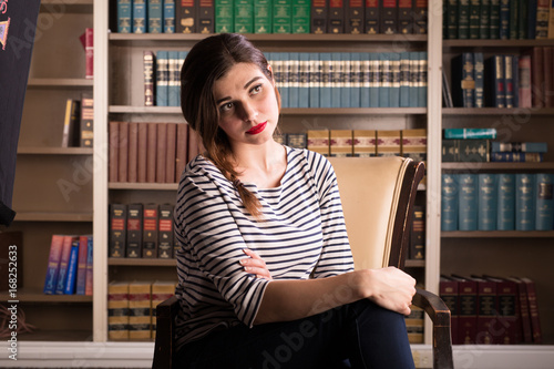 Young caucasian woman dressed like Jackie Kennedy poses in a library Poster