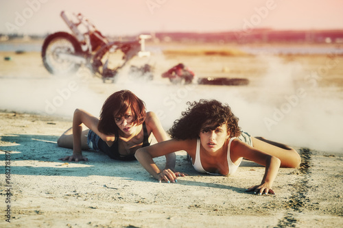 Girl lying on the ground .In the background a broken motorcycle .