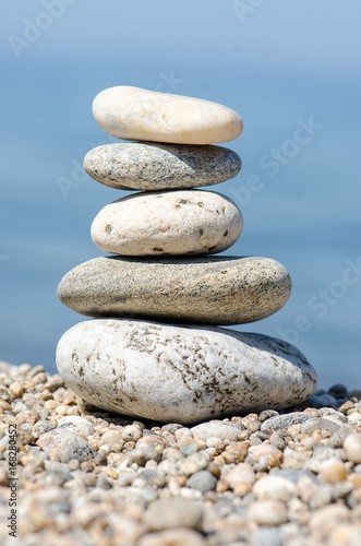 pyramid of colorful pebbles . Rock Zen in the background of the sea. Concept of harmony and balance.