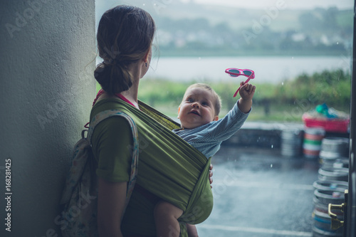 Mother with baby taking shelter from rain Poster