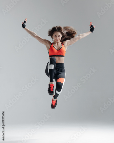 Sticker Young beautiful fitness female posing in studio