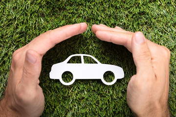 Businessman's Hands Covering Paper Car On Grass