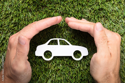Sticker Businessman's Hands Covering Paper Car On Grass
