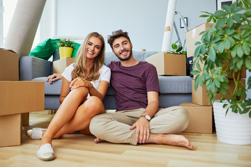 Happy young couple sitting on the floor in new apartment after moving in and looking at camera