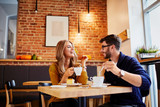 Couple of young people drinking coffee and eating cake in a stylish modern cafeteria - 168300699