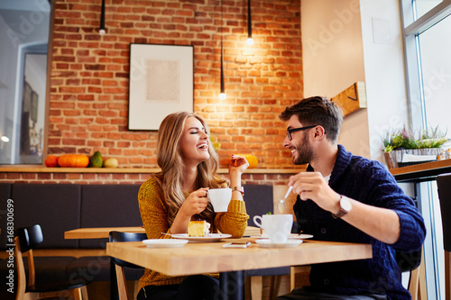 Poster Couple of young people drinking coffee and eating cake in a stylish modern cafeteria