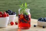 cocktail o succo con frutti di bosco in barattolo di vetro sfondo tavolo di cucina