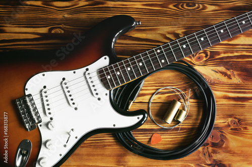 Electric guitar and guitar accessories on wooden table. Close up. Making music concept.