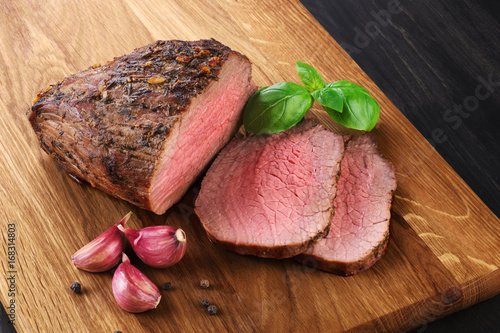 Baked meat, garlic and basil on a wooden background. Roast beef. Poster