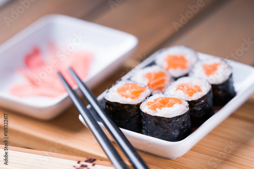 Sushi rolls with salmon, ginger and chopsticks Poster