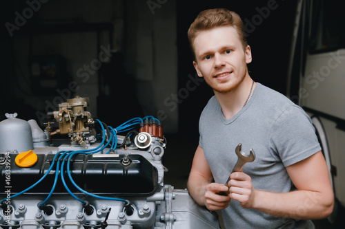 A close-up of an auto mechanic smiling repairs the engine of a lorry or bus replacement of a candle, a concept repair in a garage, a workshop Poster