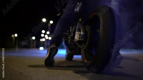 Man doing a tire burnout on motorcycle on the city road at night. Slow motion