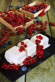 Ice cream with red currant berries. Creamy ice cream and boxes with red currants on an old wooden table. - 168366076
