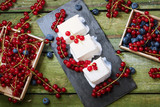 Ice cream with berries. Creamy ice cream and boxes with red currants on an old wooden table. View from above. - 168366085