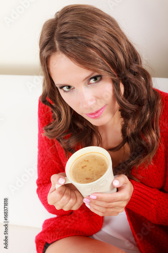 Girl red sweater holds mug with coffee