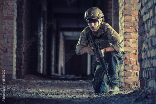 airsoft soldier with a rifle playing strikeball In brick building Poster