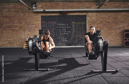 Sticker Two young sportsmen training on rowing machine