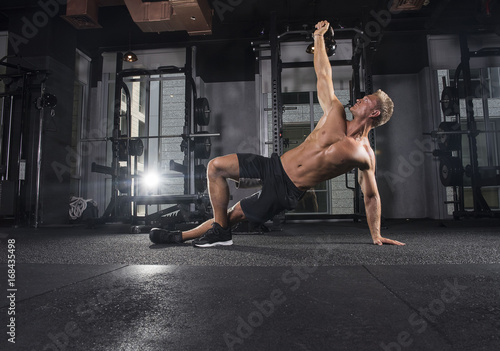 Shirtless handsome male bodybuilder athlete performs turkish getup lifts in a dark gym with alight flare behind