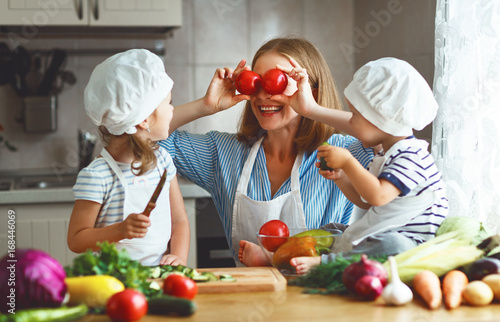 Healthy eating. Happy family mother and children prepares vegetable salad.