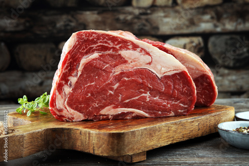 Foto op Canvas Steakhouse Raw fresh meat Ribeye Steak, seasoning and meat fork on dark background