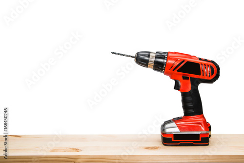 Plakat Cordless or driller lie on wooden board isolated on white background