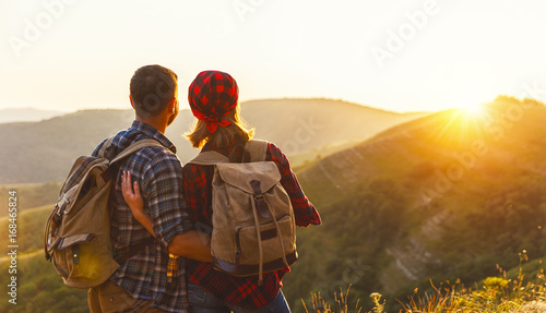 happy couple man and woman tourist at top of mountain at sunset   a hike in summer