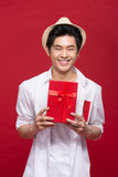 Cheerful stylish asian young male man holding a gift isolated on red background