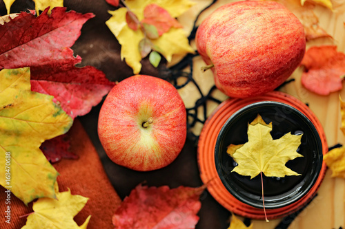 Autumn tea. Cup of tea with maple  autumn leaves, Apples and woolen rug on a wooden table. autumn mood.