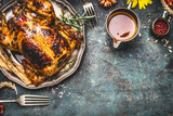 Roasted turkey with sauce served for Thanksgiving dinner on rustic table background, top view - 168473815